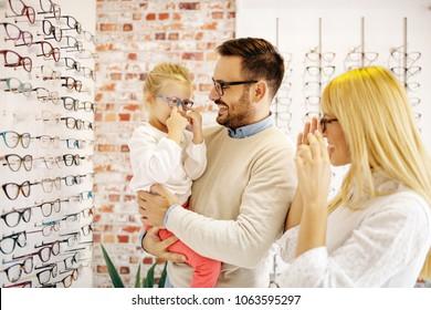 Happy family in optics store choosing glasses.