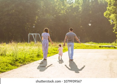 Happy family outdoor activity. Rear view of parents and baby daughter having fun and walking in summer park.