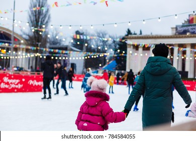 Happy family outdoor ice skating at rink winter activities