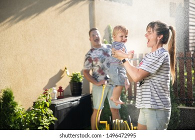 Happy family outdoor. mom, son and dad on the back yard. happy parenting concept. family splash on each other water from the hose. maternity leave. toddler boy. blond family. young family photo shoot.