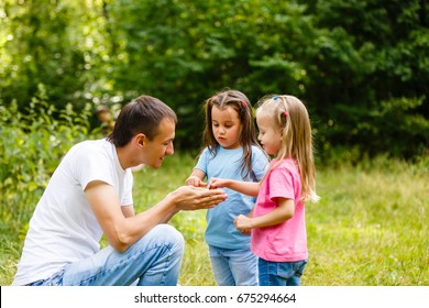 Happy family in outdoor park at sunny day. Dad and two daughters in the green garden. Group of people on green grass.