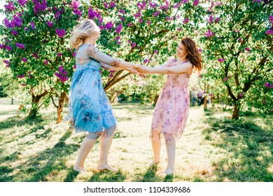 ad621349e60 Twin sisters have fun at nature. Beautiful twins in dresses dancing