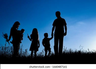 happy family outdoors in the park silhouette