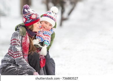 Happy family outdoors playing with snowflakes. Mother and son having fun in winter scenery