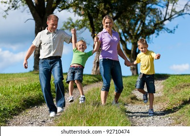 Happy family outdoors is running on a dirt path on a beautiful summer day