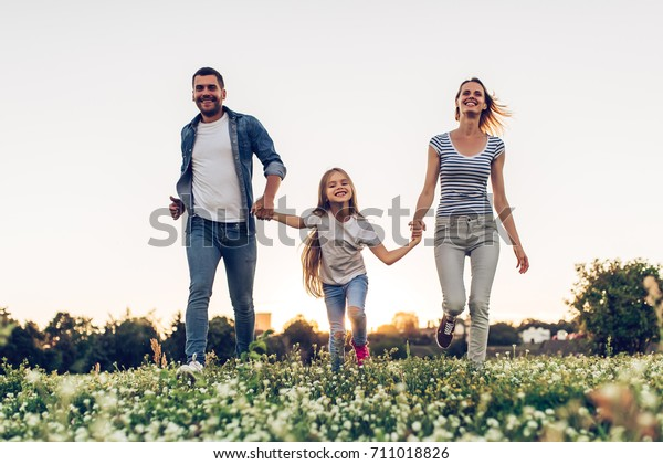 Happy family outdoors spending time together. Father, mother and daughter are having fun and running on a green floral grass during the sunset.