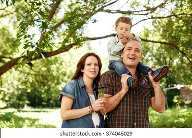 Happy Family Outdoors Walking. Pregnant Woman, Man and Little Boy Sitting on Father. Having Fun. Family Values Concept. Natural Colors.