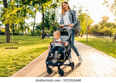 Happy family outdoors, a young mother walks with a little toddler in a stroller in the summer on nature