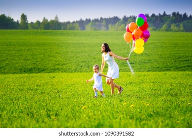 Happy family outside in summer evening. Mom and daughter running on green meadow with colorful balloons. Summer background.