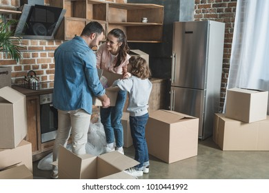 happy family packing cardboard boxes while moving home