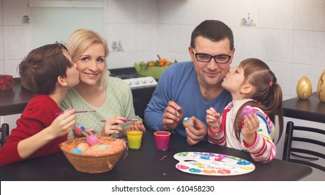 Happy family painting eggs for Easter.