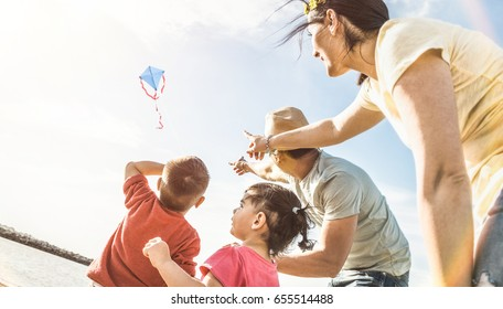 Happy family with parents and children playing together with kite at beach vacation - Summer joy happiness concept with mixed race people having candid genuine fun  - Warm vintage backlight filter