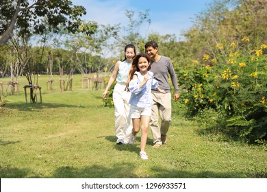 happy family parents and children are resting by walking and running in the park during summer season with clear blue sky and green trees