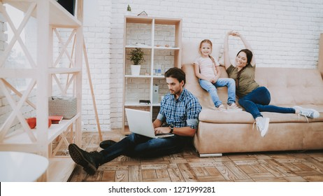 Happy Family. Parents and Daughter. Family Resting Together. Happy Child and Parents. Brown Sofa in Apartment. Working on Laptop. Man with Laptop. Smiling Family Resting. Mom with Girl Resting.