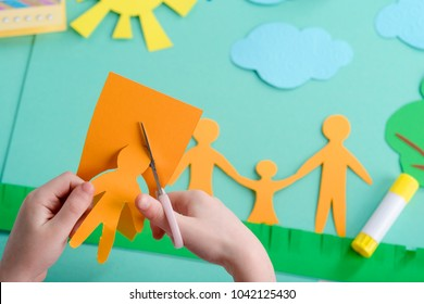 Happy family in the park. Child is cutting a shape of people, sun, tree, cloud and grass out of colored paper. Craft class in kindergarten.