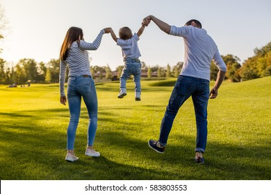 Happy family in the park evening light. The lights of a sun. Mom, dad and baby happy walk at sunset. The concept of a happy family. Parents hold the baby's hands.