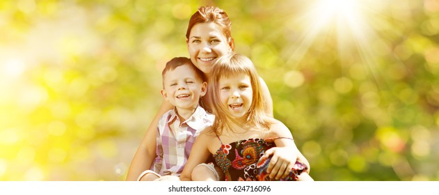 Happy family in the park. Mother, daughter and son are sitting on the grass. Woman, girl and boy playing with a cat outdoors with a colorful umbrella and birthday balloons