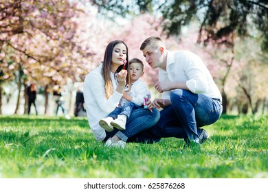 happy family in the park. mother father child son playing together outdoor and have a good mood