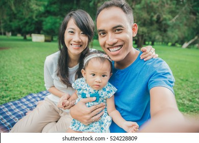 Happy family in the park taking selfie using mobile phone