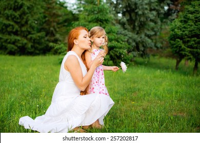 happy family in the park together with peony in hands played in beautiful summer dresses and blowing on a dandelion