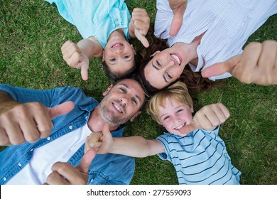 Happy family in the park together thumbs up on a sunny day