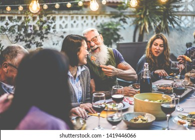 Happy family people having fun at barbecue dinner - Multiracial friends eating at bbq meal - Food, friendship, relationship and summer lifestyle concept - Focus on hipster man face