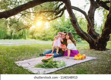 Happy family picnicking in the garden at sunset