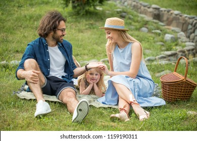 happy Family picnicking outdoors with their cute daughter in park, blue clothes, woman in hat
