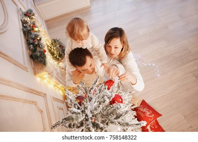Happy family placing Christmas tree decoration on the top of Christmas tree. Parents lifting child to help her decorate Christmas tree. Happy christmas holiday