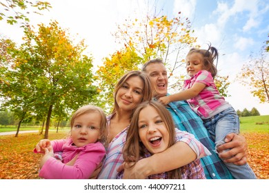 Happy family play in autumn park hug little kids