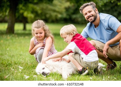 Happy family play together with dog at park