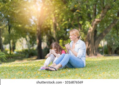 Happy family playing in autumn park outdoors concept. Lifestyle portrait mom and daughter in happiness at the outside in the meadow