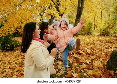 Happy family playing in the autumn in the park.