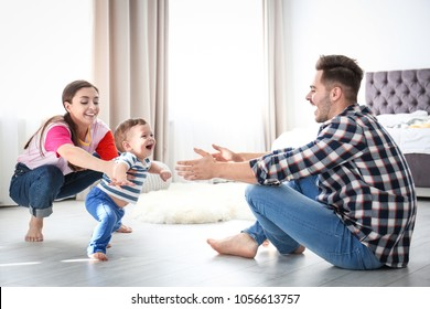 Happy family playing and baby learning to walk at home