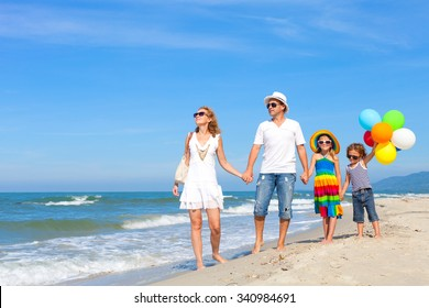 Happy family playing  with balloons on the beach at the day time. Concept of friendly family.