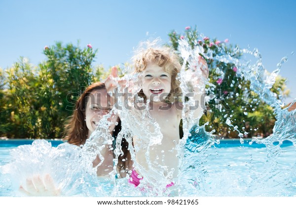 Fröhliche Familie spielt in blauem Wasser des Swimmingpools auf einem tropischen Resort am Meer. Sommerurlaubskonzept
