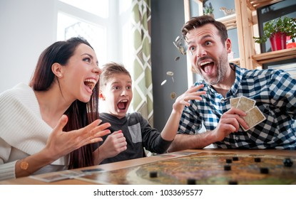 Happy family playing board game at home, boy throwing elements after winning