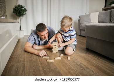 happy family is playing a board game at home. dad and son are playing a fun game. the concept of happiness. table games. hobby.