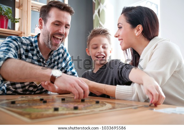 Happy family playing board game at home, happiness concept