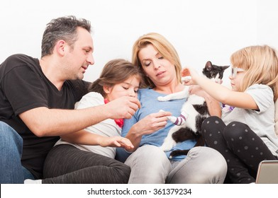 Happy family playing with cat or pet sitting on the couch or sofa