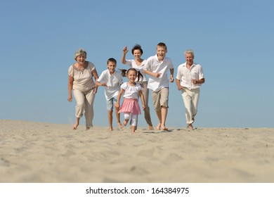 happy family playing catch-up on the sand in the summer