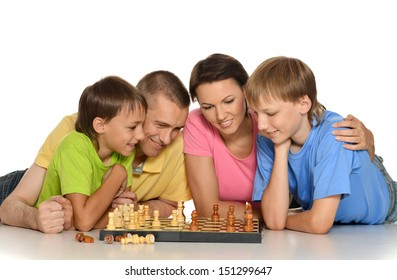 Happy family playing chess lying on the floor