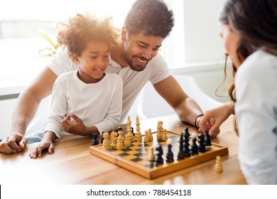 Happy family playing chess together