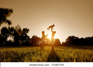 Happy family playing with a child at sunset in the park.