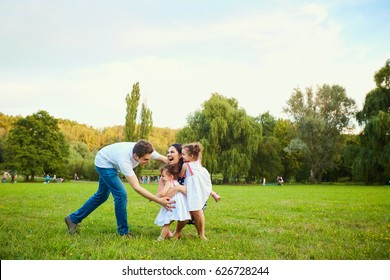 Happy family playing with children in the park.