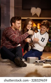 Happy family playing with dachshund puppy received for christmas.