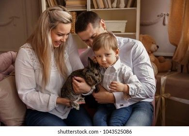 Happy family playing with Easter bunny and celebrating Easter day. Portrait of mother, father and son at Easter sunday. Domestic life of young family