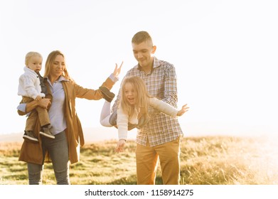 happy family playing in the green field at sunset