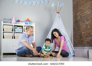Happy family playing at home near a tent together
