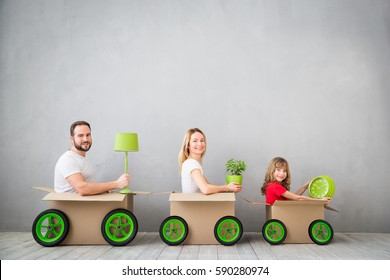 Happy family playing into new home. Father, mother and child having fun together. Moving house day and express delivery concept